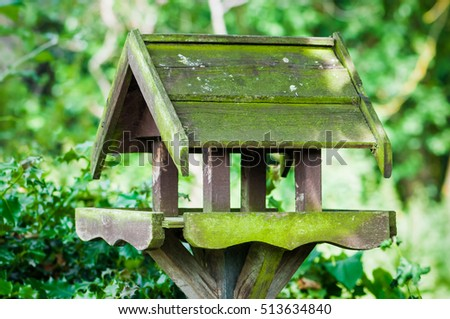Bird feeder house shaped garden accessory weathered covered in moss