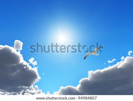 Bird in a bright blue sky with soft clouds - stock photo