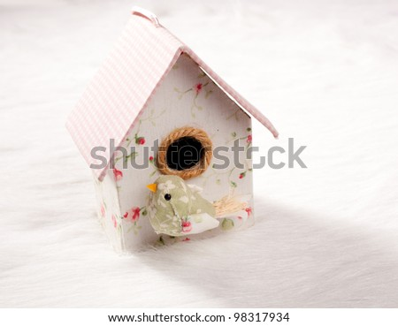 bird in a nest fabric house with round window in pastel colors - stock photo
