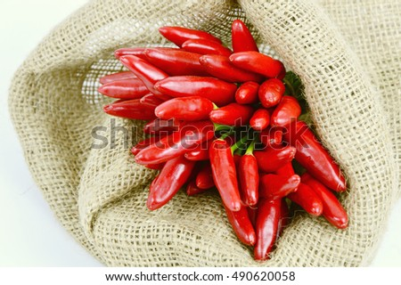 Bird's eye chili or red chili peppers group in sack cloth bag with white background. The pepper heat helps to stimulate secretions  clearing your nose,  antibacterial.