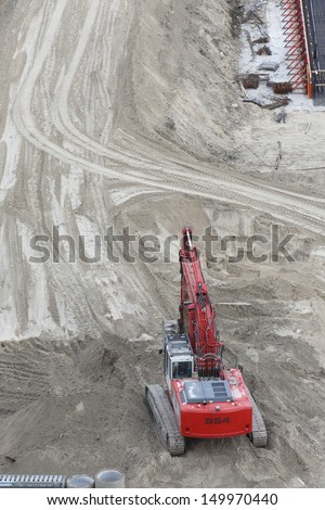 bird's eye fiew of a red digger in sand on a construction area - stock photo
