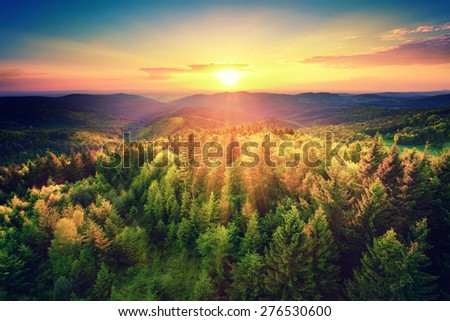 Bird's-eye view of a scenic sunset over the   forest hills, with toned dramatic colors - stock photo