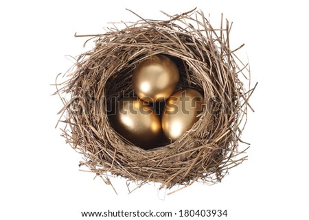 Bird's nest with three golden eggs, cut out on white background - stock photo