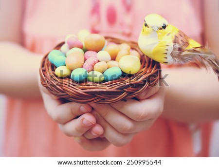 Bird sitting in a small basket on a pile of candies - stock photo
