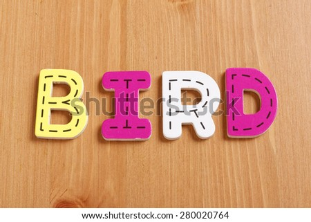 BIRD, spell by woody puzzle letters with woody background - stock photo