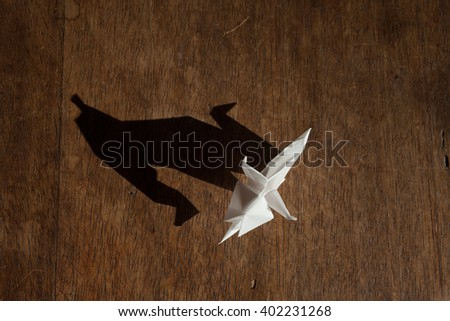 Bird view of an origami elephant made of white paper over wooden background. - stock photo