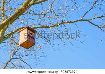 Birdhouse. Handmade wooden bird house hanging in the branches of a tree - stock photo
