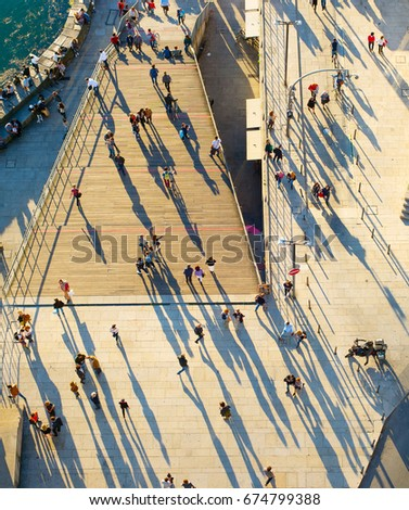 Birds-eye view of a people walking on the street at sunset