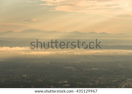 Birds eye view of city of Chiang Mai with buildings  , mountain on the background in the morning