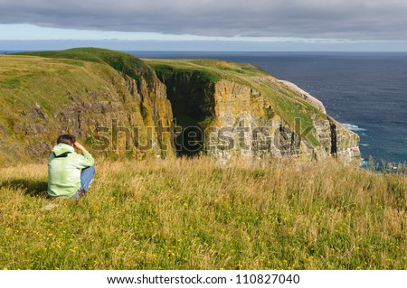Birdwatcher on Cape St Mary's in Newfoundland - stock photo