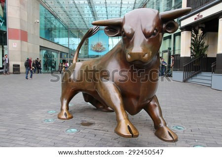 BIRMINGHAM, UK - APRIL 24, 2013: People walk past Bull sculpture at Bull Ring in Birmingham. The famous bronze sculpture was created by Laurence Broderick.