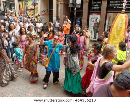 BIRMINGHAM UK - JULY 24: The cart festival 'Ratha yatra' in Birmingham July 24, 2016. Many people happily dancing in the festival in front of colored cart with Jagannatha on narrow Cannon Street.
