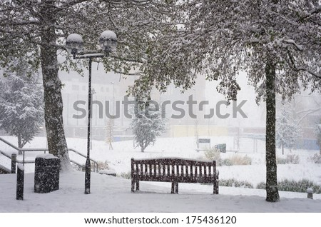 BIRMINGHAM, UNITED KINGDOM - NOVEMBER 18, 2010: Bench in a snow covered Aston University campus in Birmingham UK during the winter snowstorm of 2010. The storm brought widespread chaos across the UK. - stock photo
