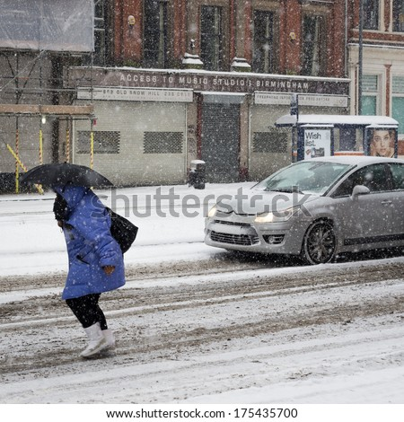 BIRMINGHAM, UNITED KINGDOM - NOVEMBER 18, 2010: Woman with an umbrella bracing the snow storm during the 2010 winter in Birmingham, UK. The snow brought widespread travel disruption. - stock photo
