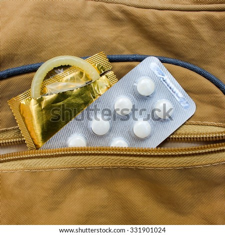 birth control pill and condom peeking out from pocket handbags - stock photo