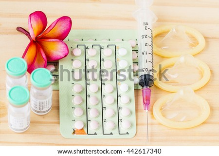 birth control pills ,injection medicine , syring ,condom with frangipani flower. oral contraception concept  - stock photo