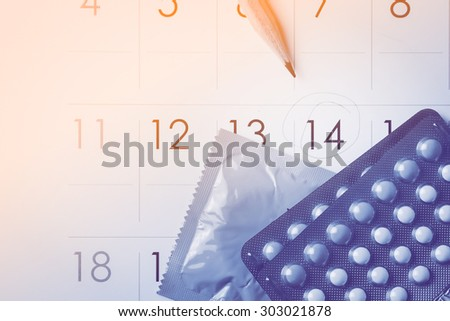 Birth control pills on calendar concept for save sex on day 14 (add vignette tone) - stock photo