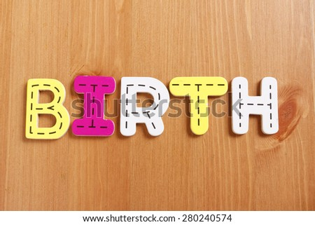 BIRTH, spell by woody puzzle letters with woody background - stock photo