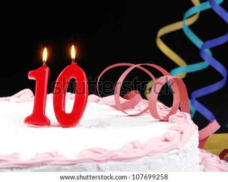 Birthday-anniversary cake with red candle showing Nr. 10 - stock photo