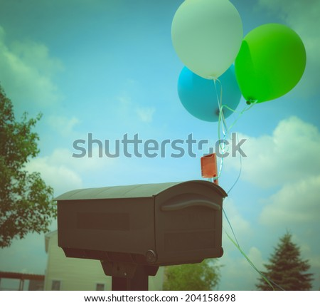 Birthday balloons attached to a milbox for people know where is the birthday party - stock photo
