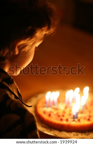 Birthday Boy - The only light in the room comes fron the lighted candles. - stock photo