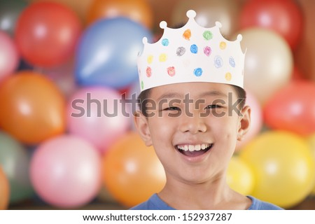 Birthday Boy Wearing a Crown in Front of Balloons