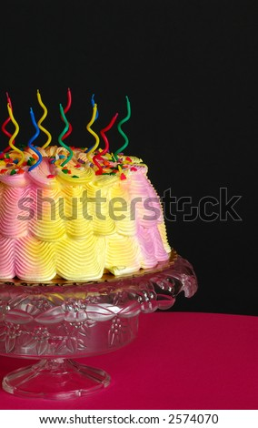 Birthday Cake - A pink and yellow iced birthday cake with unlit swirly candles on top sits in front of a black background.
