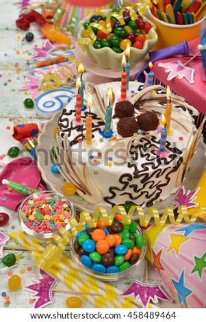 Birthday cake and various accessories on a white background