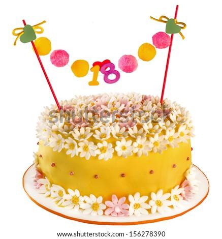 Birthday cake celebrating eighteen years, covering of flowers and daisies. Anniversary or birthday - stock photo