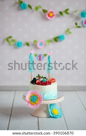Birthday cake decorated with fruits and a garland with the inscription 1 on a support on a white wooden floor. A flower garland on the wall. - stock photo