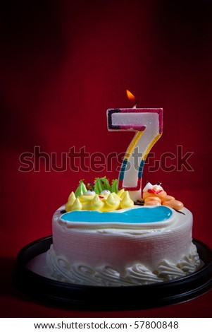 birthday cake  lit candle for a seventh birthday or anniversary celebration. - stock photo