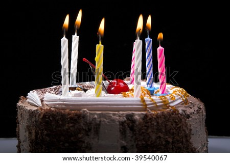 birthday cake with candle isolated on black - stock photo