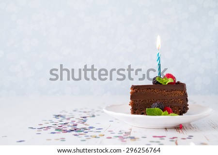 Birthday cake with candle, light blue background, bokeh