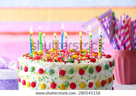 Birthday cake with candle on colorful striped background - stock photo