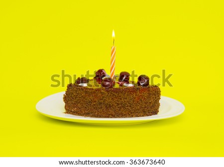 Birthday cake with candle on yellow background