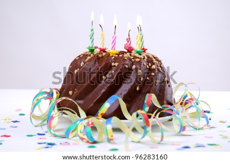 birthday cake with candles,confetti and streamers - stock photo