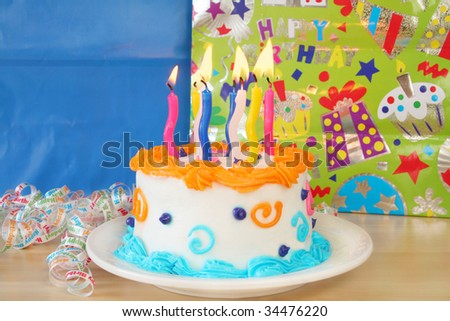 Birthday cake with candles lit and packages in the background with room for your text. Used a shallow depth of field and selective focus being on the lit candles.