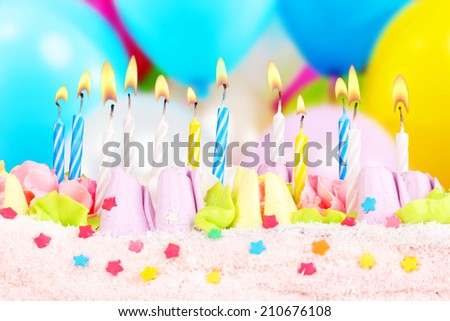 Birthday cake with candles on bright background - stock photo