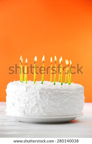 Birthday cake with candles on color background - stock photo