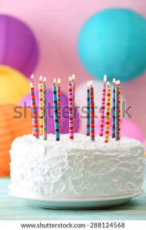 Birthday cake with candles on colorful background - stock photo