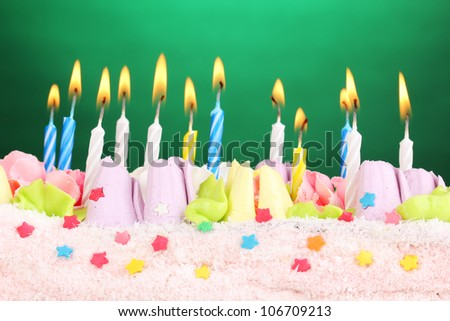 Birthday cake with candles on green background