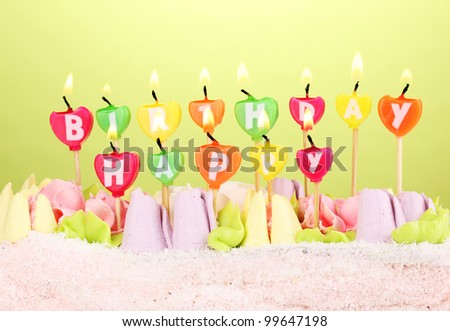 Birthday cake with candles on green background - stock photo