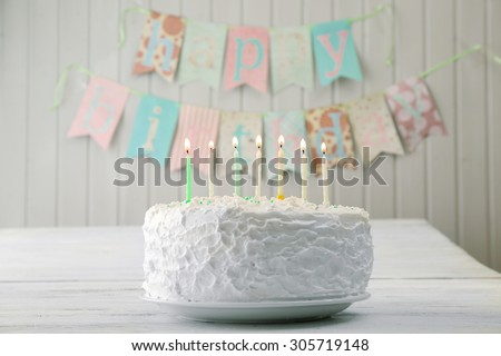 Birthday cake with candles on planks wall background - stock photo