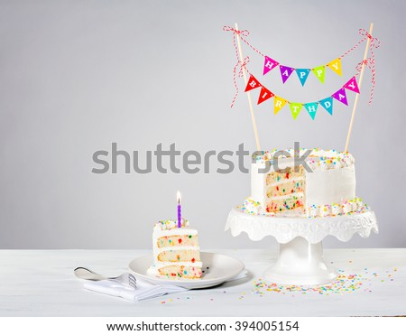 Birthday cake with colorful bunting and sprinkles