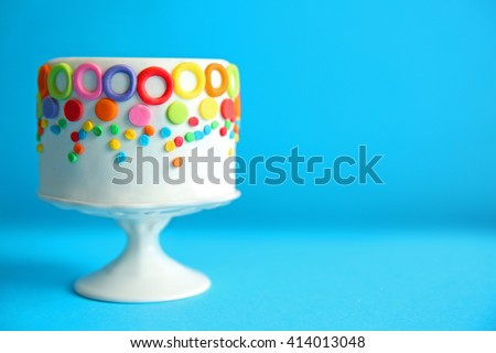 Birthday cake with colorful decorations on blue background. - stock photo