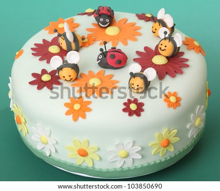 Birthday cake with flowers, sugar bees and ladybugs - stock photo