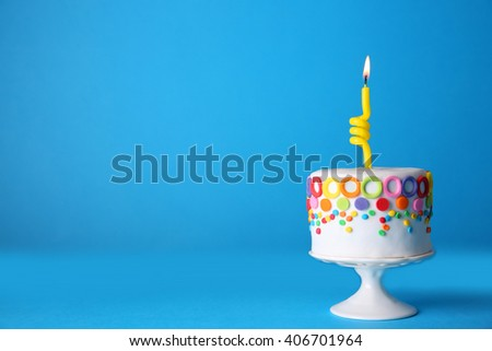 Birthday cake with one candle on blue background. - stock photo
