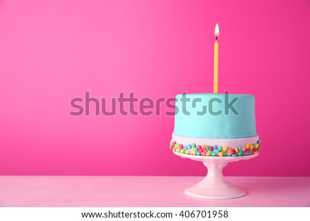 Birthday cake with one candle on pink background. - stock photo