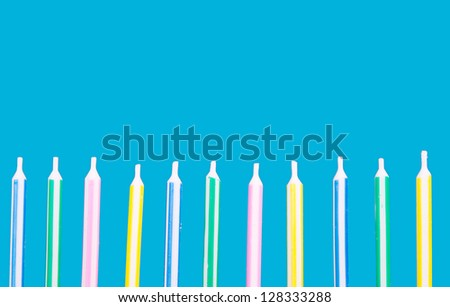 Birthday candles in a row on a blue background - stock photo