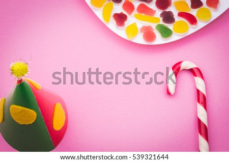 Birthday cap and candy on a light violet background/Birthday cap and candy